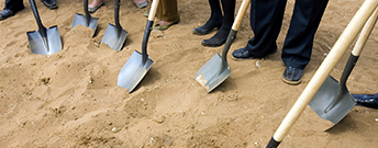 shovels in dirt breaking ground